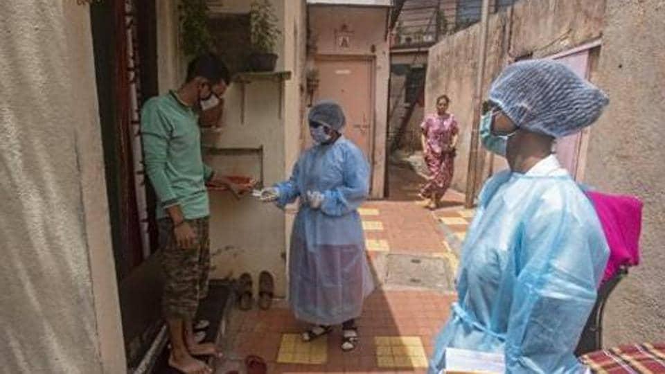 Health workers during a door to door screening for coronavirus in a slum near Dandekar bridge in Pune.