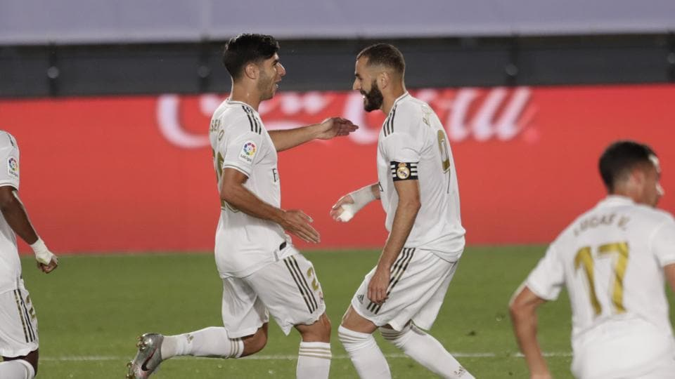 Real Madrid's Karim Benzema, right, celebrates after scoring a penalty against Deportivo Alaves with his teammate Marco Asensio during the Spanish La Liga soccer match between Real Madrid and Deportivo Alaves at the Alfredo di Stefano stadium in Madrid, Spain, Friday, July 10, 2020. (AP Photo/Bernat Armangue)