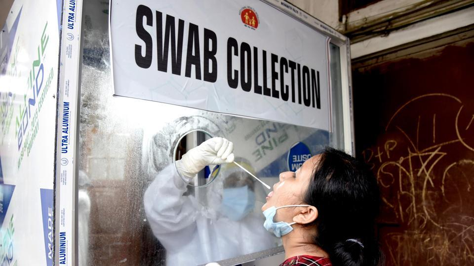 A healthcare worker collects swab sample from a woman for COVID-19 testing in Guwahati on Sunday. (ANI Photo)