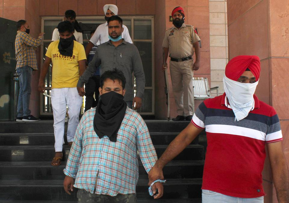 Police with three men who were arrested on Sunday for their involvement in a bank robbery in Mohali on June 17.