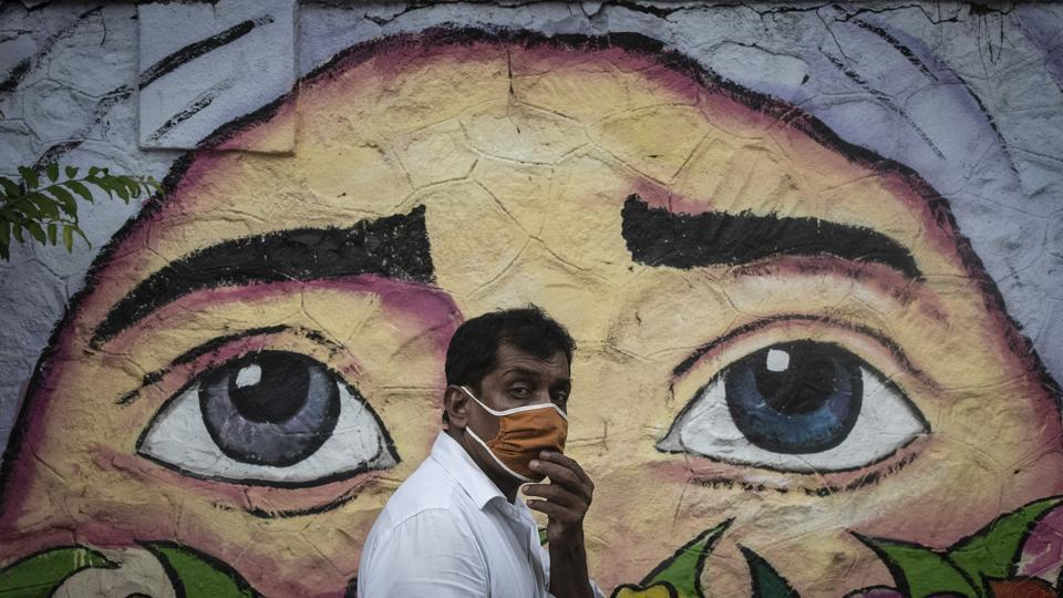 A man wearing a protective face mask walks past a wall graffiti in Pune on June 11. 28,637 new cases of the coronavirus disease (Covid-19) fuelled another record jump that pushed India's case tally past 8.49 lakh as of the morning of July 12, according to Union Health Ministry data. (Pratham Gokhale / HT Photo)