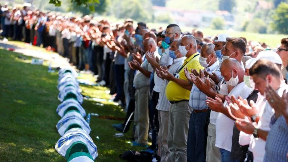People pray near coffins at a graveyard during a mass funeral in Potocari near Srebrenica, Bosnia and Herzegovina . Bosnia marks the 25th anniversary of the massacre of more than 8,000 Bosnian Muslim men and boys, with many relatives unable to attend due to the coronavirus disease (COVID-19) outbreak. REUTERS/Dado Ruvic
