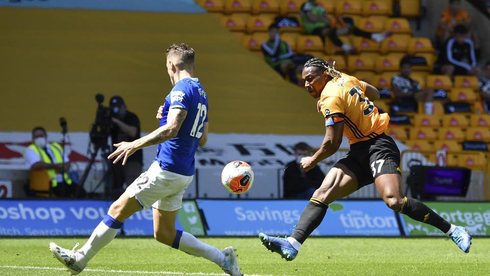 Everton's Lucas Digne, left, tries to block a shot from Wolverhampton Wanderers' Adama Traore during the English Premier League soccer match between Watford and Everton at the Molineux Stadium in Wolverhampton, England, Sunday, July 12, 2020.