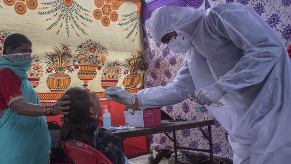 A doctor takes a swab sample of a Mumbai resident during a Covid-19 testing drive, on Saturday.