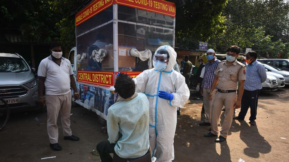 A healthcare worker wearing PPE suit collects swab sample from a man to test for coronavirus infection at Ajmeri Gate in New Delhi, on Saturday.
