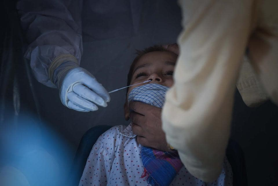 A health worker collects a swab sample from a child to test for coronavirus infection at Khajuri Khas in New Delhi.