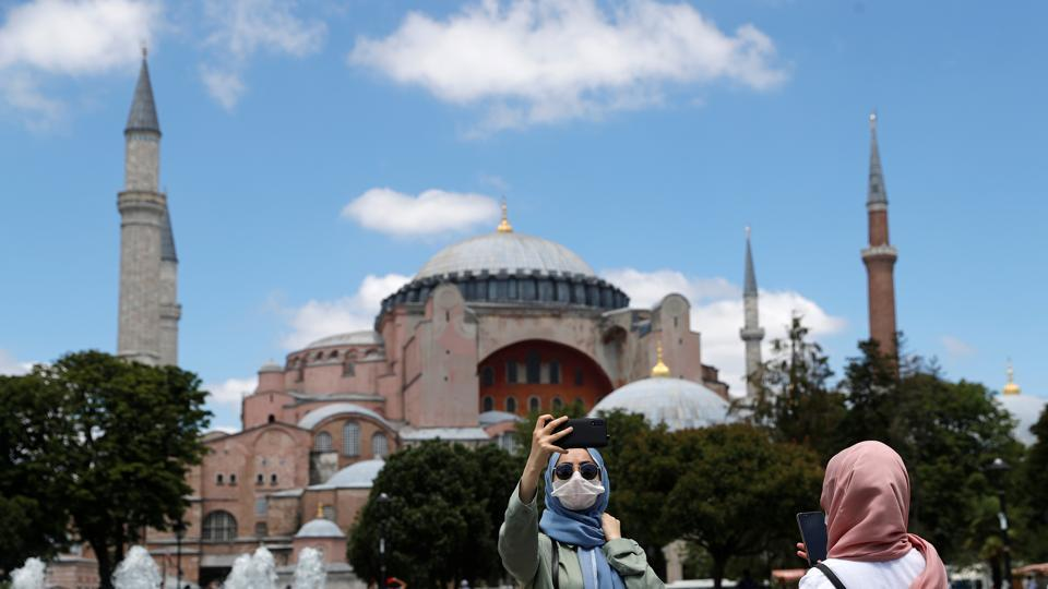 A woman poses for a selfie in front of Hagia Sophia, or Ayasofya-i Kebir Camii, which the Turkish president declared to be open to Muslim worship after a court ruling, in Istanbul, Turkey, July 11, 2020.