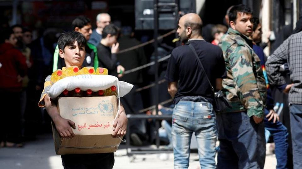 A boy holds a cardboard box of food aid received from World Food Programme in Aleppo's Kalasa district, Syria.