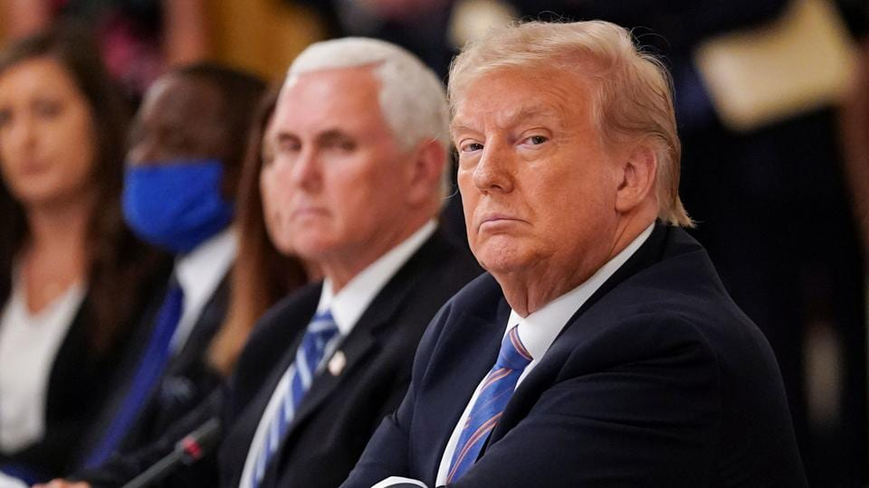 US President Donald Trump is seated next to Vice President Mike Pence as he listens during an event on reopening schools amid the coronavirus disease (COVID-19) pandemic in the East Room at the White House in Washington.