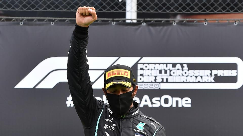 Formula One F1 - Steiermark Grand Prix - Red Bull Ring, Spielberg, Styria, Austria - July 12, 2020 Mercedes' Lewis Hamilton wears a protective face mask as he celebrates winning the race on the podium with the trophy, following the resumption of F1 after the outbreak of the coronavirus disease (COVID-19)