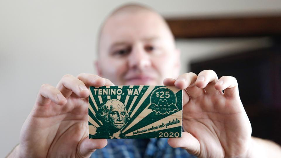Mayor Wayne Fournier holds $25 in wooden money, in Tenino, Washington . Tenino's small businesses were struggling to survive due to Covid-19, so local officials revived an unconventional idea from the last century: print its own currency on planks of wood.