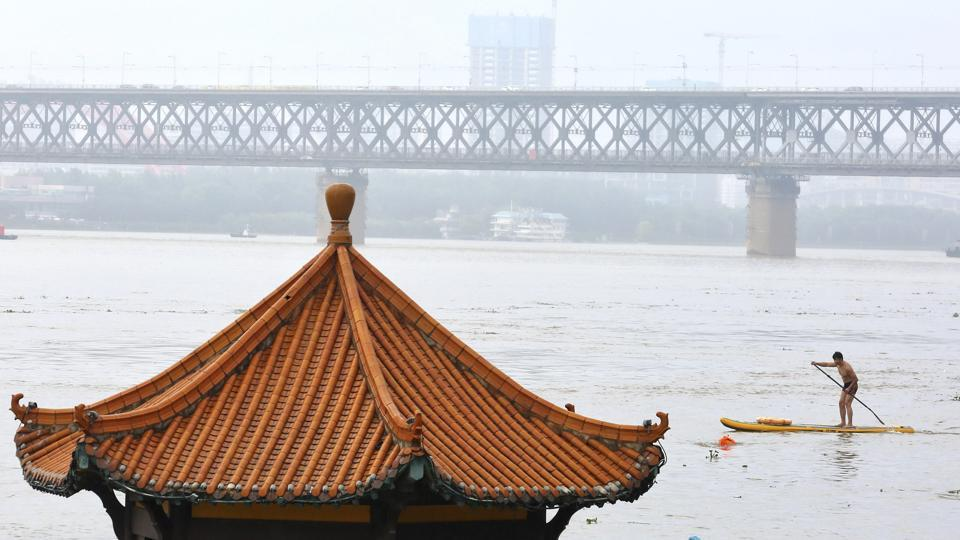 Residents swim past a riverside pavilion submerged by the flooded Yangtze River in Wuhan in central China's Hubei province Wednesday, July 8, 2020.