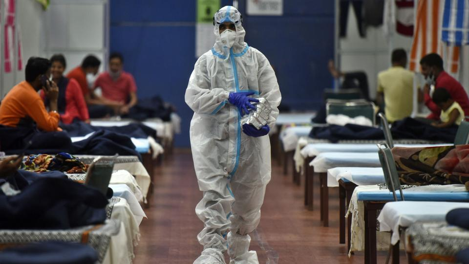 A health worker in PPE serving food to Covid-19 patients housed at the Commonwealth Games Village Sports Complex which is a temporary coronavirus care centre at Patparganj in New Delhi.