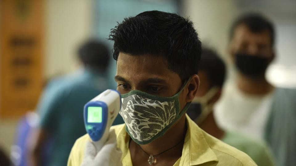 A health worker uses an infrared thermometer thermal screen a man during swab sample collection for coronavirus testing in Gurugram, Haryana.