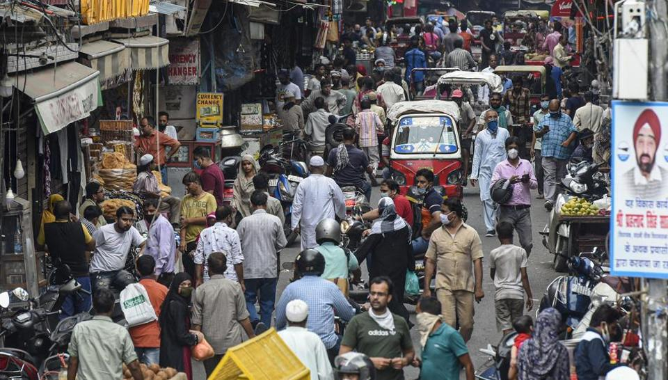 Pedestrians and vehicles jostle for space in a crowded street leading to no social distancing at Jama Masjid market in New Delhi on Wednesday.