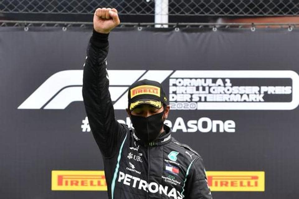 Mercedes' Lewis Hamilton wears a protective face mask as he celebrates winning the race on the podium with the trophy, following the resumption of F1 after the outbreak of the coronavirus disease (COVID-19) Joe Klamar/Pool via REUTERS