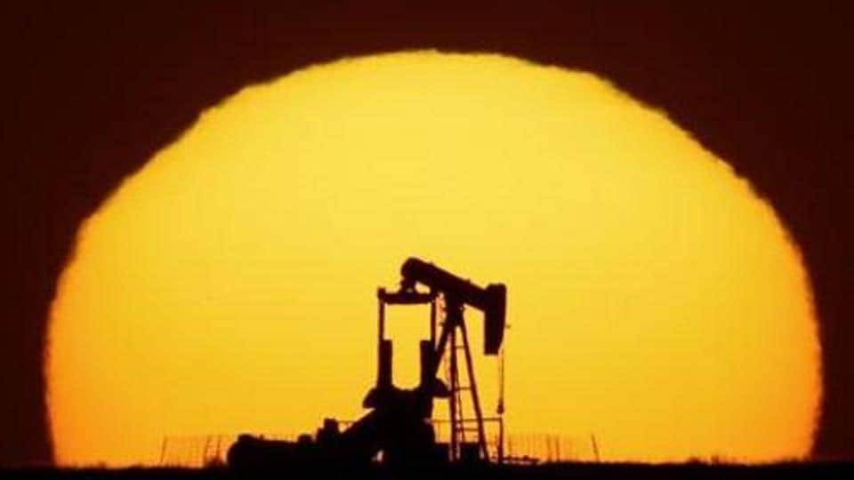 An idle oil pumping unit is silhouetted against the setting sun.