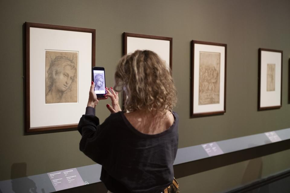 A visitor wearing a face mask to protect against coronavirus, takes a photo of Italian painter Giovanni Antonio Sogliani's art work at the exhibition From Durer to Matisse Selected drawings