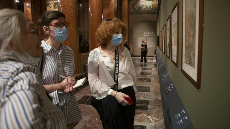 Visitors wearing face masks, look at the exhibition From Durer to Matisse Selected drawings from the collection of the Pushkin State Museum of Fine Arts in Moscow, Russia.  (AP PHOTO/Alexander Zemlianichenko Jr)