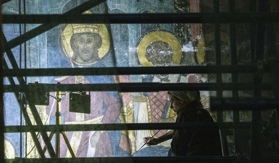 a restorer works inside the Dormition Cathedral in the Kremlin in Moscow, Russia, Friday, July 10, 2020. (AP)