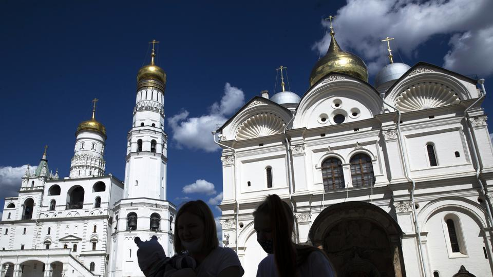People visit Cathedral Square of the Kremlin in Moscow, Russia, with the Ivan the Great Bell Tower, left and the Cathedral of the Archangel, right in the background, Friday, July 10, 2020.  (AP)