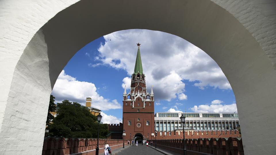 A woman walks on the Troitsky Bridge in the Kremlin in Moscow, Russia, Friday, July 10, 2020, with the Troitskaya Tower in the background. The first Russian monument to become part of UNESCO world heritage 30 years ago, Moscow's Kremlin Museums struggle to finance restoration works amid coronavirus outbreak and move freeze most of the projects until the next year.  (AP)
