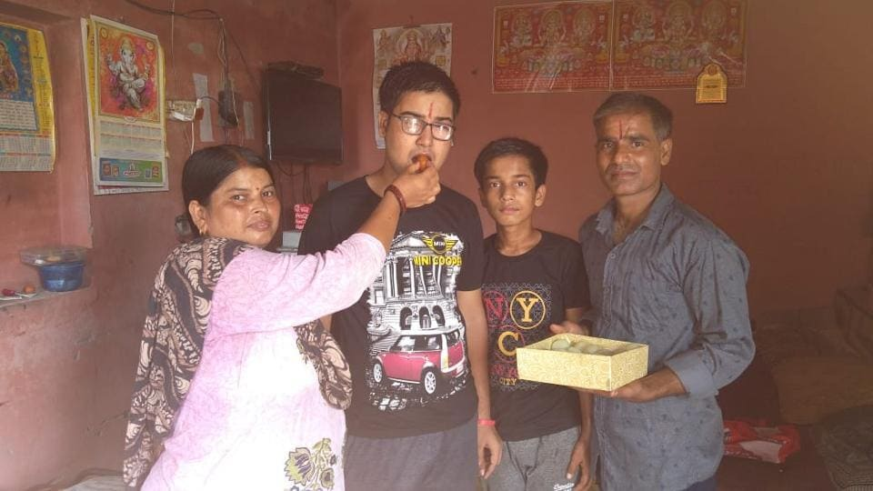 Topper, Kishore Kumar, celebrating his score with his parents in Kurali on Wednesday. His parents run a tea stall.