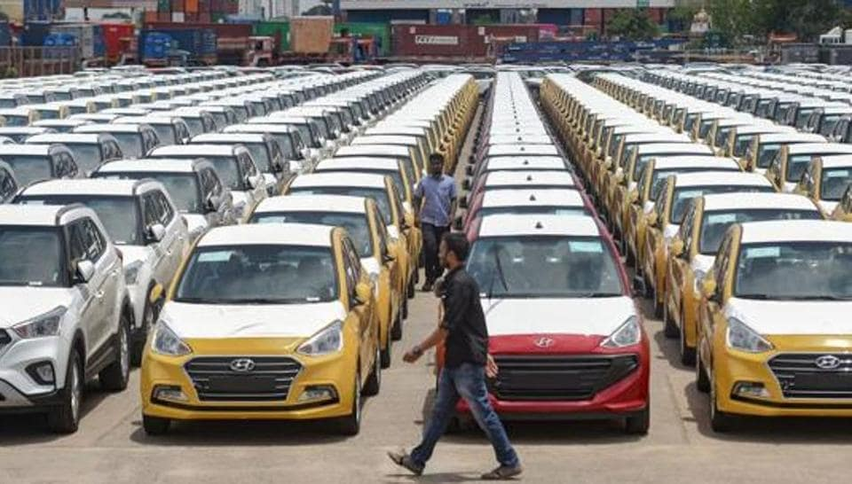 Cars are seen parked in a dock at the Chennai Port Trust. Domestic sales of passenger cars, utility vehicles, and vans fell 49.6% from a year earlier in June.