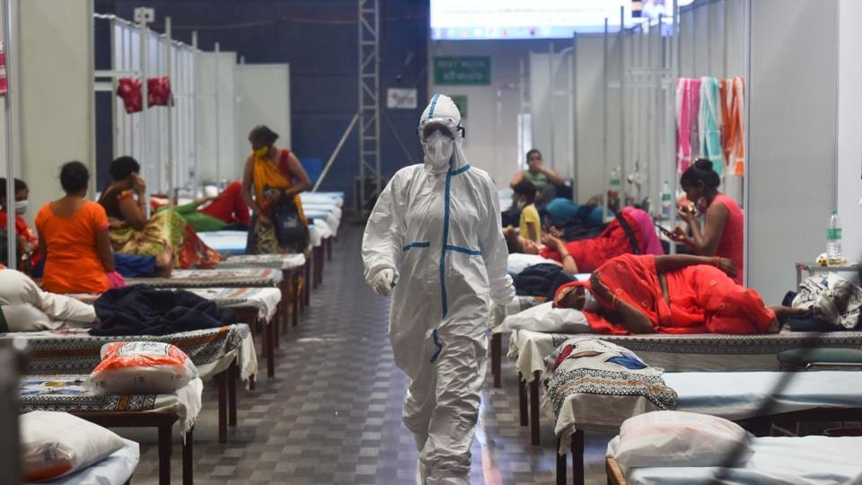A health worker in PPE walks past Covid-19 patient housed inside the Commonwealth Games Village Sports Complex which is temporarily converted into a coronavirus care centre at Patparganj in New Delhi on Tuesday.