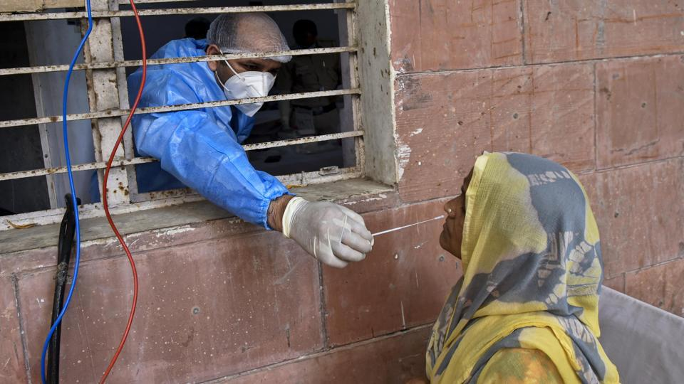 A health worker collects a swab sample from a woman to test for Covid-19 infection at a dispensary in Okhla, New Delhi on Tuesday.