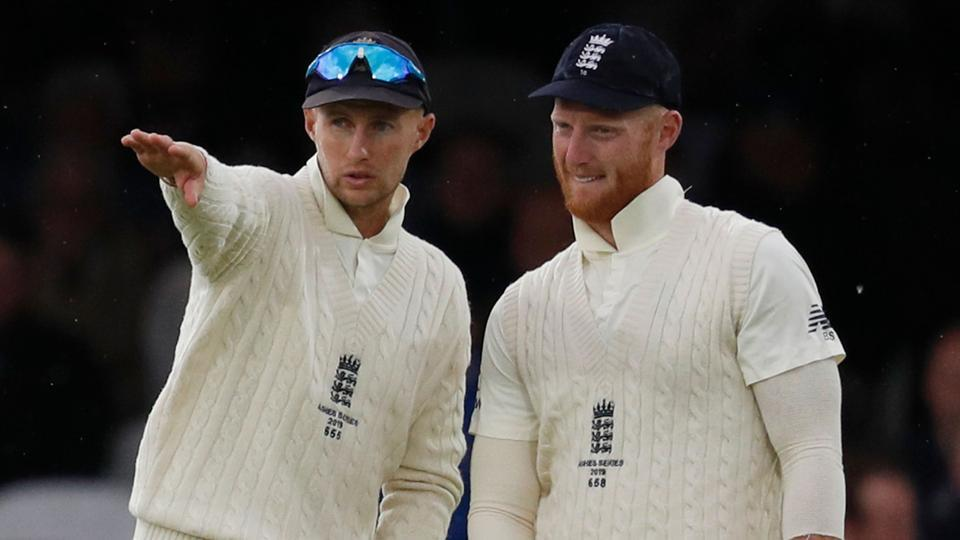 (FILES) In this file photo taken on August 16, 2019 England's captain Joe Root (L) and England's Ben Stokes talk between balls on