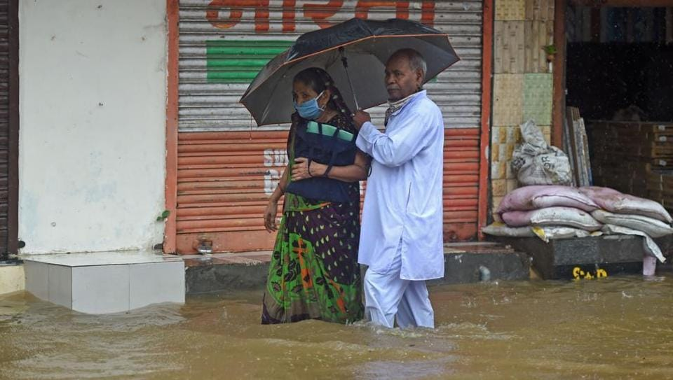 An elderly couple wade through a flooded street during rain in Mumbai on July 15. Incessant rains and water logging marked the day on July 15  across Mumbai and its suburbs, with traffic thrown out of gear and daily routines brought to a crawl. (Punit Paranjpe / AFP)