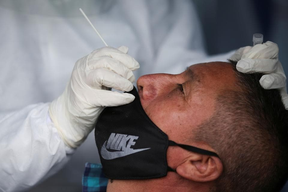 A medical team member takes a swab sample from a man to be tested for the coronavirus disease (COVID-19) in one of the neighbourhoods where the mayor's office decreed strict quarantine, amidst an outbreak of the coronavirus disease (COVID-19), in Bogota, Colombia July 14, 2020.