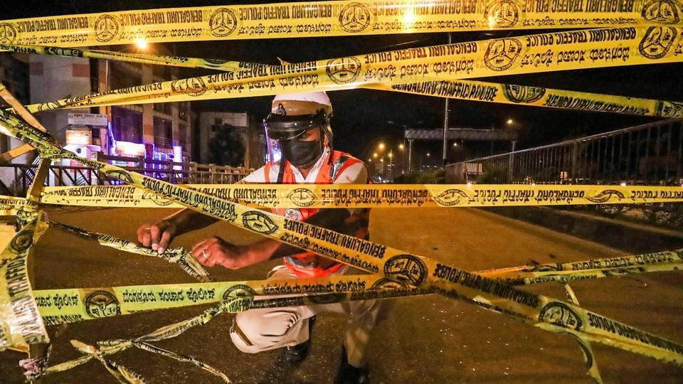 A traffic cop seals a road ahead of total lockdown, during Unlock 2.0 in Bengaluru on Tuesday.