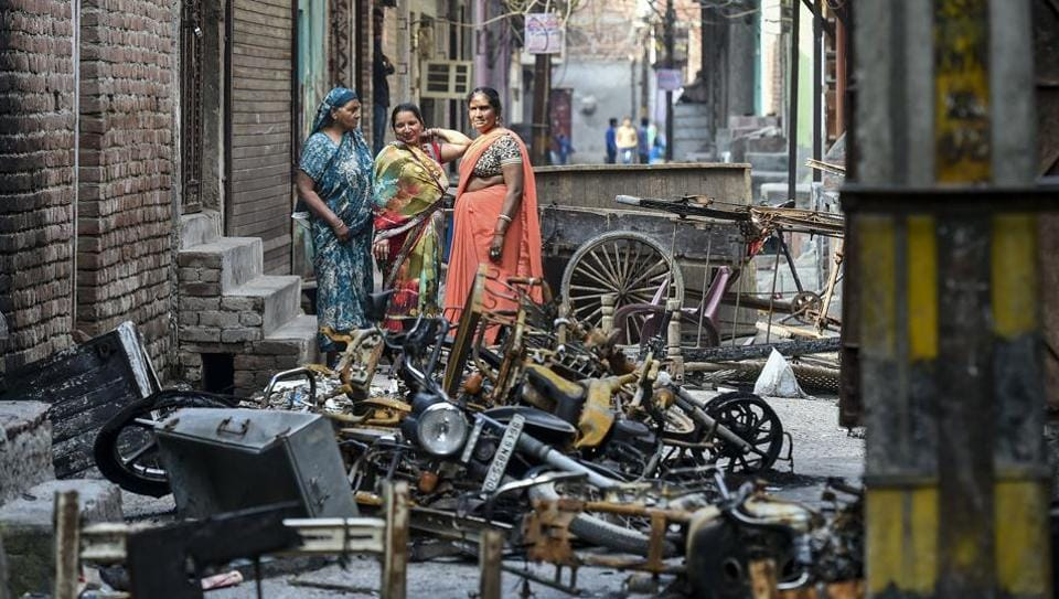 Women stand beside charred remains of vehicles and vandalised properties at Shiv Vihar in northeast Delhi on March 2, 2020.