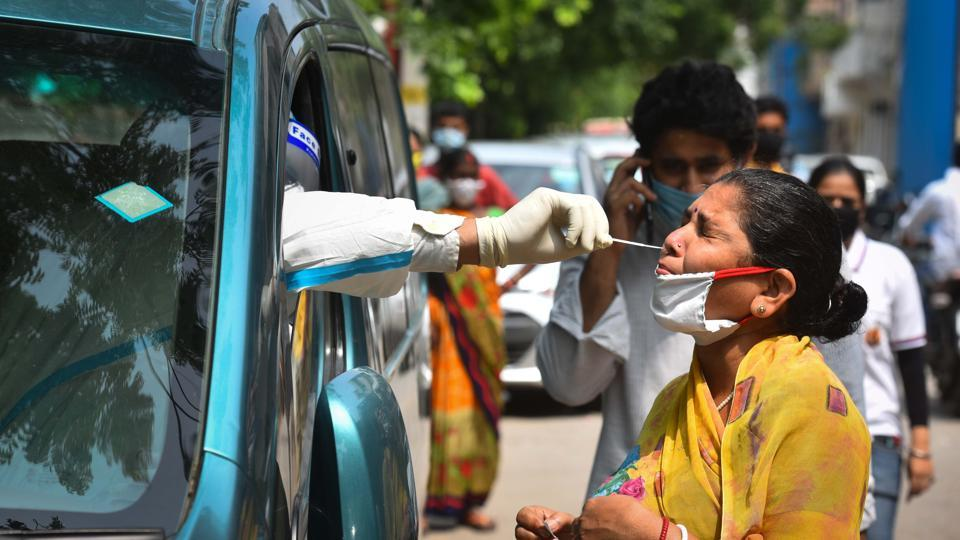 A health worker of Special Mobile Surveillance team in PPE coveralls collects a swab sample from a woman for Covid-19 rapid antigen test at Model Town in New Delhi on Wednesday.