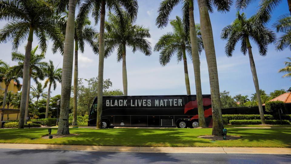 A team bus carrying the NBA champions Toronto Raptors basketball team, with Black Lives Matter displayed on the sides, arrives at the Walt Disney World complex outside Orlando, Florida.