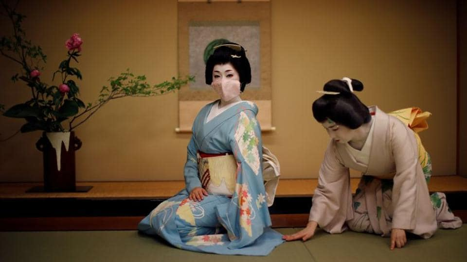 Koiku, who is a geisha, is seen wearing a protective face mask while her colleague Mayu adjusts her kimono before a performance in Tokyo on June 23. The number of geisha - famed for their witty conversation, beauty and skill at traditional arts - has been falling for years. Moreover, due to the coronavirus outbreak, many of them have been without work for months and now operate under awkward social distancing rules. (Kim Kyung-Hoon / REUTERS)