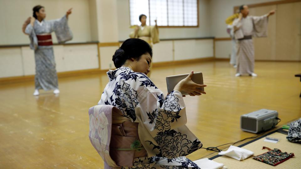 Mayu uses a tablet to film her fellow geisha practising a dance routine during a class in Tokyo on July 13. Engagements are down 95%, and come with new rules: no pouring drinks for customers or touching them even to shake hands, and sitting 2 metres apart. Masks are hard to wear with their elaborate wigs, so they mostly don't. (Kim Kyung-Hoon / REUTERS)