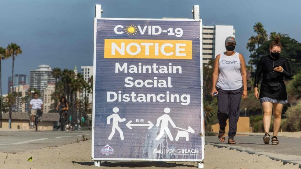 Women wearing facemasks walk near a notice about maintaining social distance on the beach in Long Beach, California.