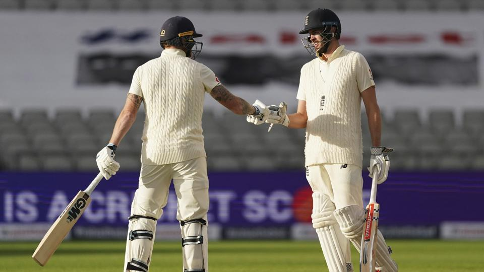 Ben Stokes, left, and Dom Sibley tap their gloves at the end of the first day of the second cricket Test match between England and West Indies at Old Trafford in Manchester, England.