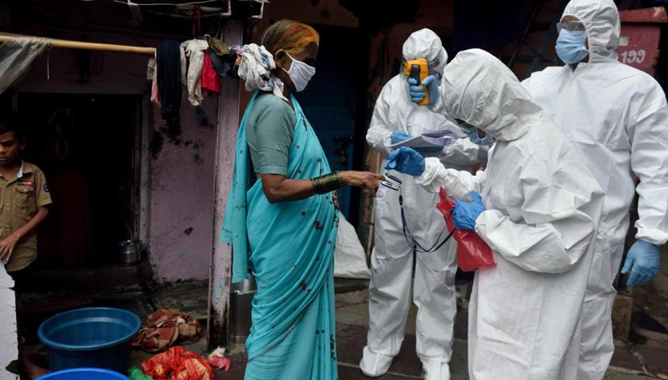 A BMC health care worker checks the temperature of the resident at Dharavi during Covid-19 pandemic in Mumbai on Thursday.