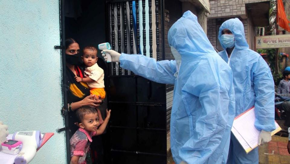 Health worker check temperature of a resident at Milind Nagar, Yogidham during Covid-19 pandemic in Kalyan, Mumbai on Tuesday.
