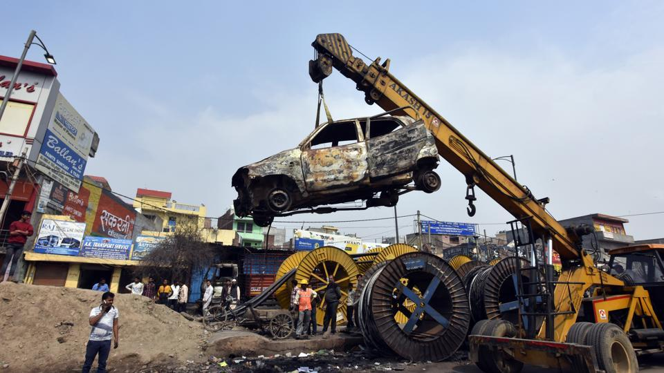 Charred vehicles are carried using a crane following violent clashes in North East Delhi over the new citizenship law at Chand Bagh, in New Delhi on February 29, 2020.