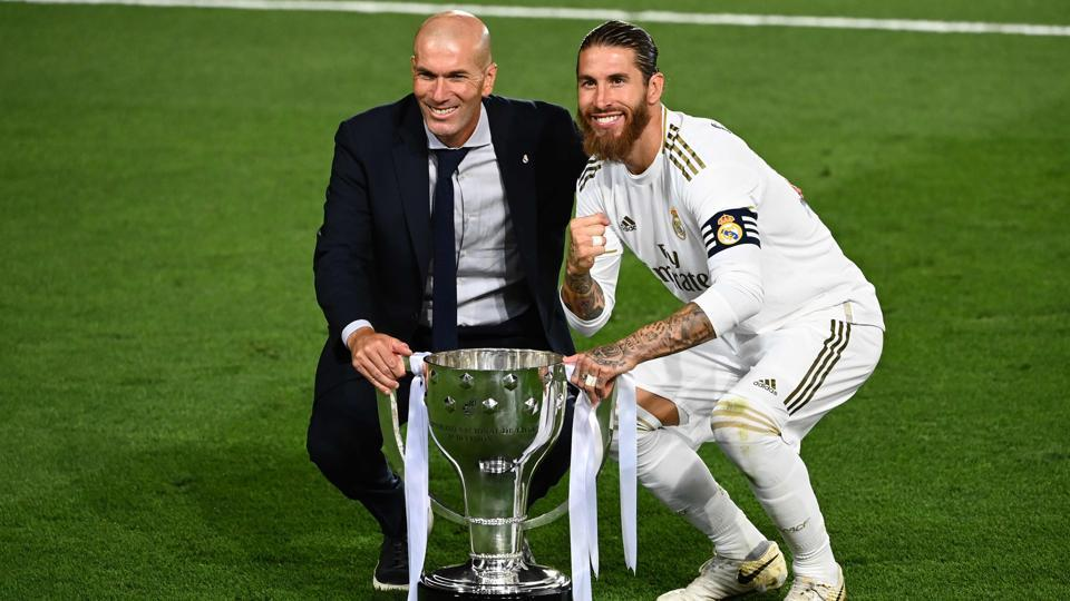 Real Madrid's French coach Zinedine Zidane and Real Madrid's Spanish defender Sergio Ramos celebrate with the trophy after winning the Liga title after the Spanish League football match between Real Madrid CF and Villarreal CF at the Alfredo di Stefano stadium in Valdebebas, on the outskirts of Madrid, on July 16, 2020.