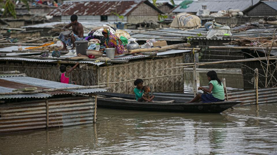 A flood affected family takes shelter on the roof of their partially submerged house along river Brahmaputra in Morigaon district, Assam on Thursday.