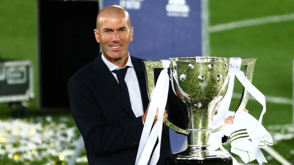 Real Madrid coach Zinedine Zidane celebrates with the trophy after winning La Liga.