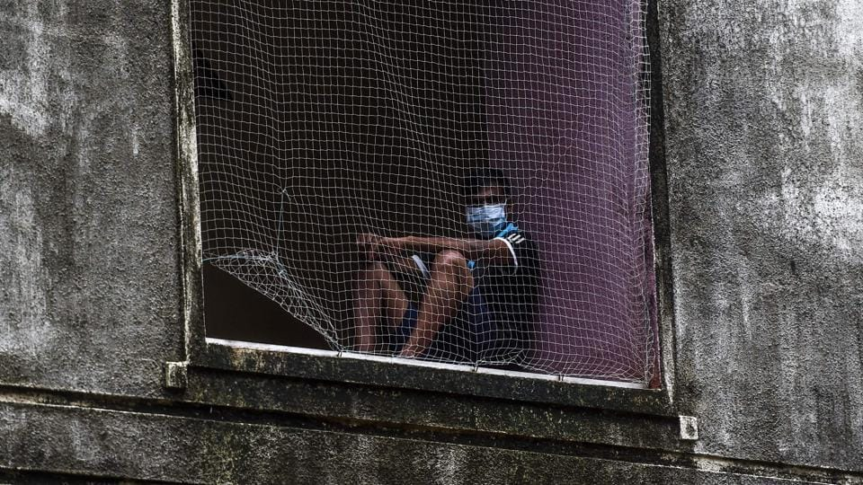 A patient wearing a facemask sits watching behind a net while recovering from the COVID-19 coronavirus at a care centre in Mumbai on July 16. A total of 690 new fatalities recorded on July 16 have now taken the disease death toll in the four-and-a-half months of the outbreak's sweep across India  to 25,594. (Punit Paranjpe / AFP)