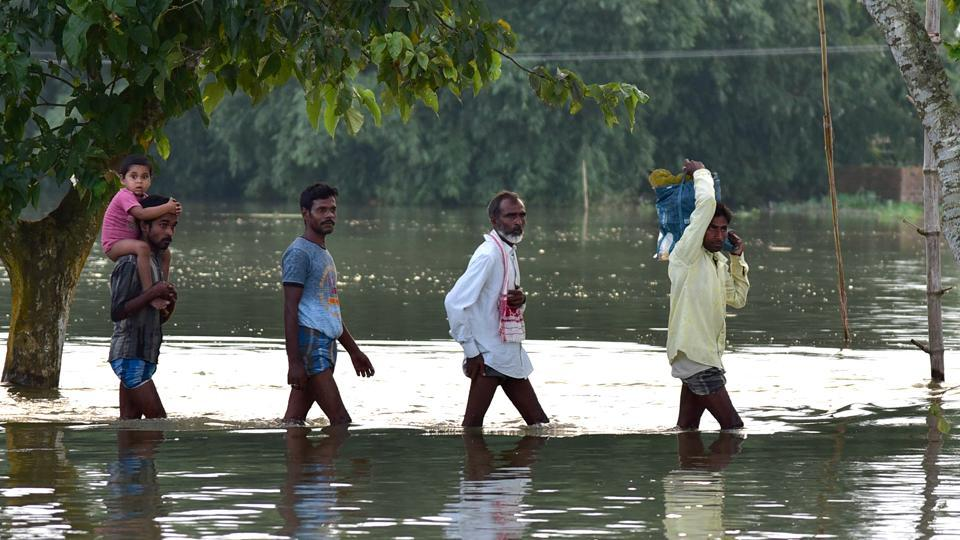 Villagers cross a road submerged in water in the flood-affected area of Nagarbera in Assam on July 17. Nearly 40 lakh people in 27 of Assam's 33 districts are affected by the deluge, an official bulletin said on July 16. (ANI)