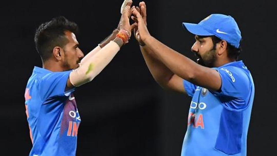 India's Yuzvendra Chahal (L) and Rohit Sharma celebrate the wicket of New Zealand's captain Kane Williamson during the first Twenty20 cricket match between New Zealand and India in Wellington on February 6, 2019.